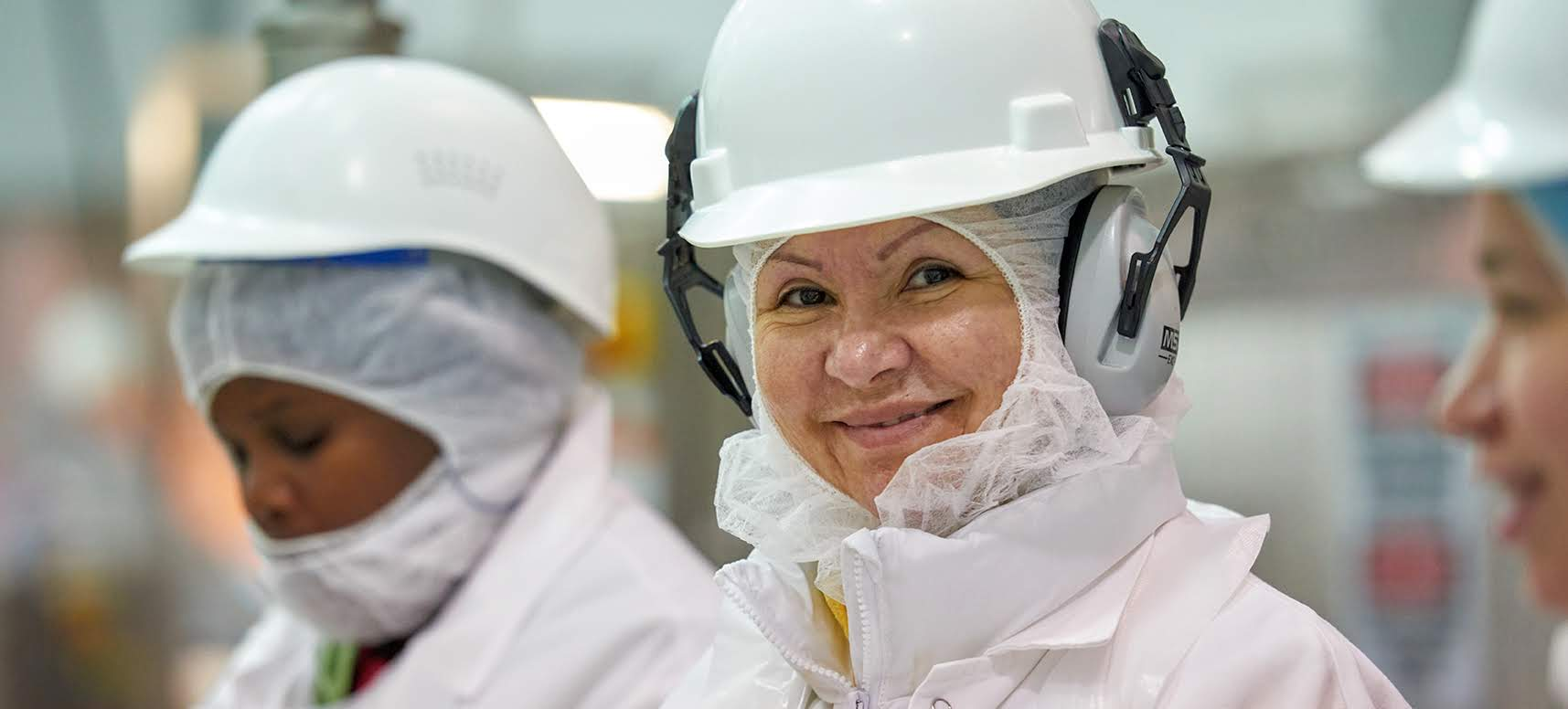 Two plant workers in white protective gear smiling