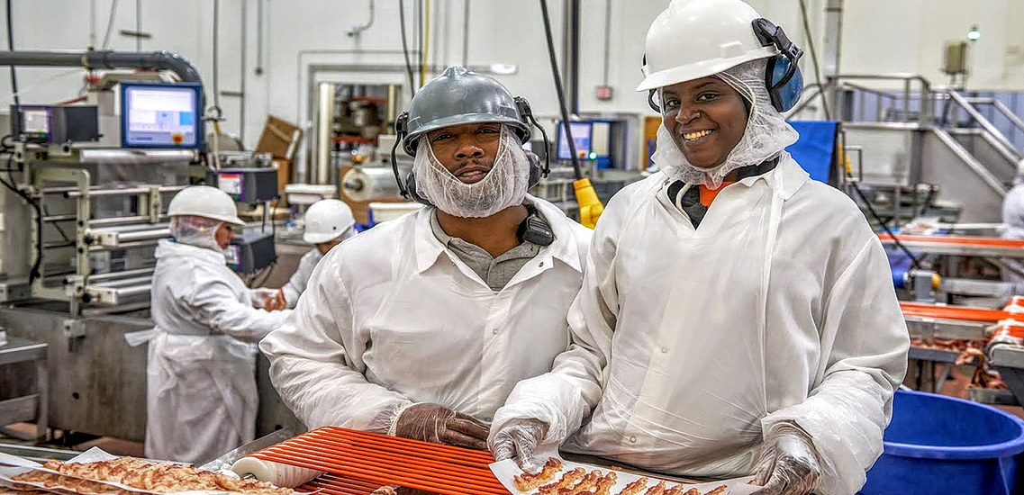 Two plant workers on the bacon line wearing white protection clothes smiling